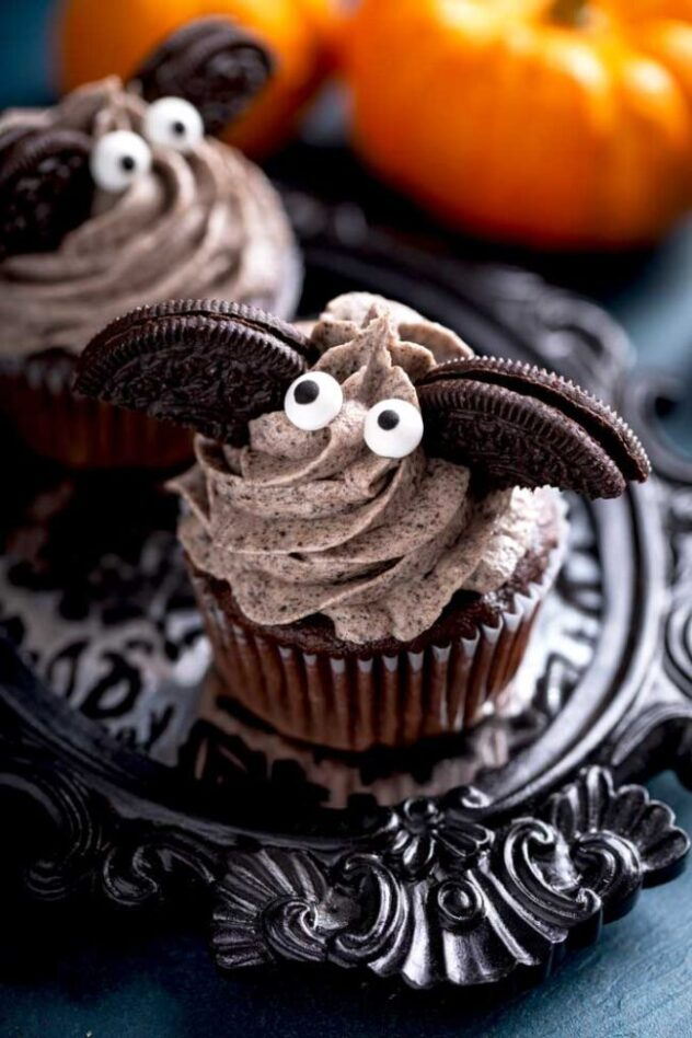 Chocolate cupcakes frosted with a white frosting that contains crumbled oreos to make it appear brown, are topped with two eyes, and two half oreos to create a bat on top of these Halloween themed cupcakes.