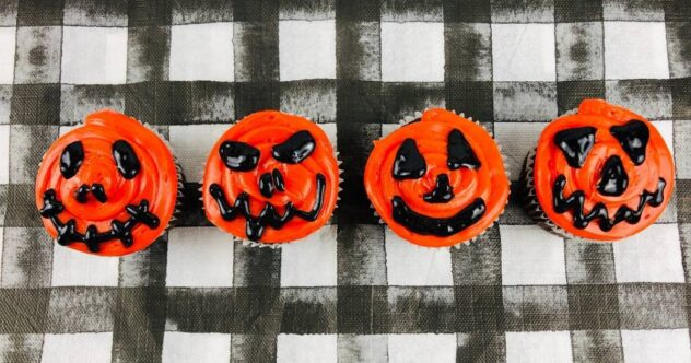 Four orange frosted cupcakes with Jack-o-lantern faces painted with black frosting make a simple and effective Halloween themed cupcake.
