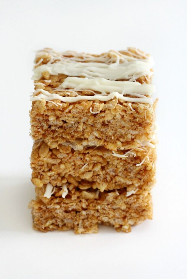 Tannish and orangeish rice krispie treats cut into squares, stacked three high.  On top of each square, stripes of white frosting are clearly visible.