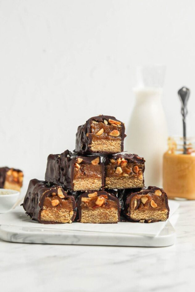 A stack of snickers bars arranged on a plate.  The ends of the bar are open exposing the layer of nougat, caramel, and peanuts encased inside the chocolate coating.