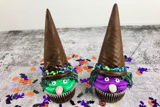 Two witches, one with a green face, and one with a purple face, are made from frosting, nuts, and candy eyes on top of chocolate cupcakes.  Their faces are surrounded by squiggly black and green hair made from frosting,.  The entire cuipcake is crowned with a chocolate dipped cone and a cookie to create a pointed witches hat.  This is a fun Halloween themed cupcake.