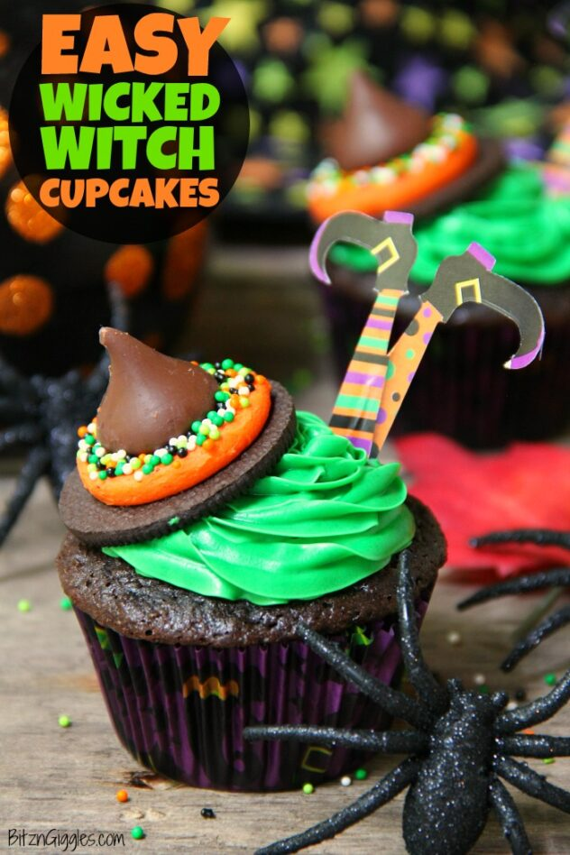 A chocolate frosted cookie with a chocolate kiss embeded in orange frosting is poised atop a green frosting swirl.  Two paper legs with witches shoes on them and mismatched stockings (both orange, but one is striped with black, green, and purple, while the other has polka dots of the same colors) stick out of the cupcake opposite the hat giving the impression that a witch has crash landed on this Halloween themed cupcake.