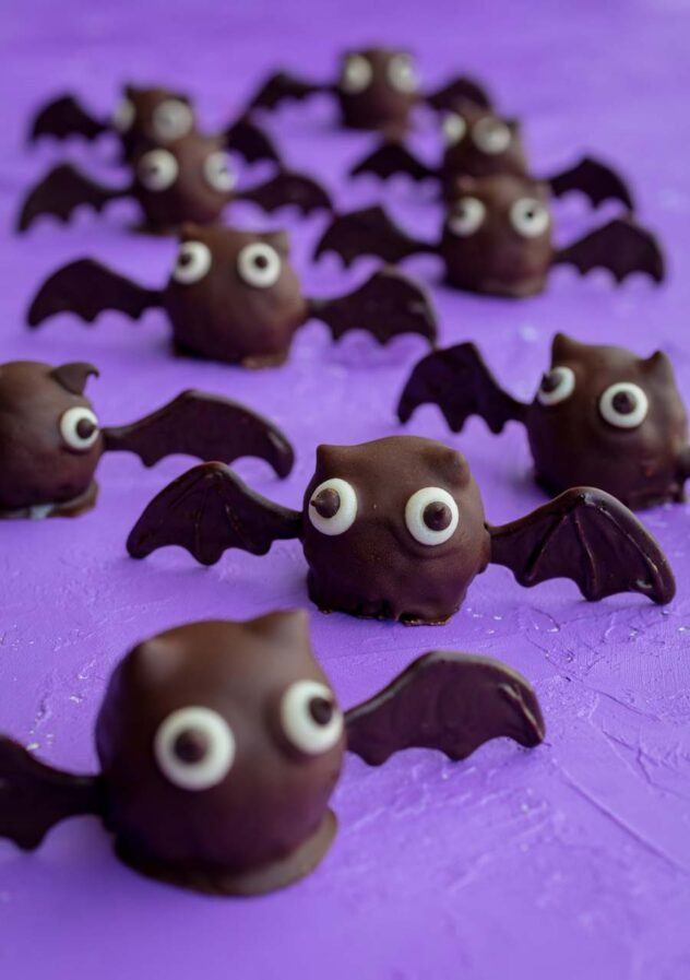 A group of round brown chocolate truffles with two candy eyes placed on front with a chocolate bat wing inserted on each side.  The bats are arranged on a purple textured surface.