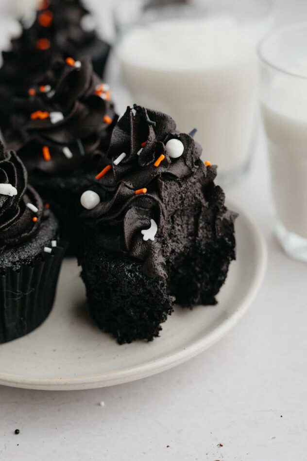 Black Velvet cupcakes (very black) topped with black frosting that's been sprinkled with edible white pearls, ghosts, and a few orange and white sprinkles create an elegant Halloween themed cupcake.