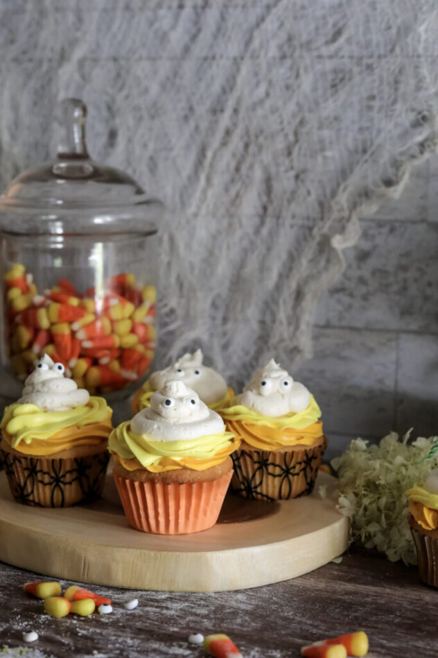 A wooden board topped with four cupcakes that are frosted with a layer of orange frosting, topped with a layer of yellow frosting and finally topped with white frosting with eyes on it to resemble a ghost.   In the background is a large glass jar filled with candy corn.