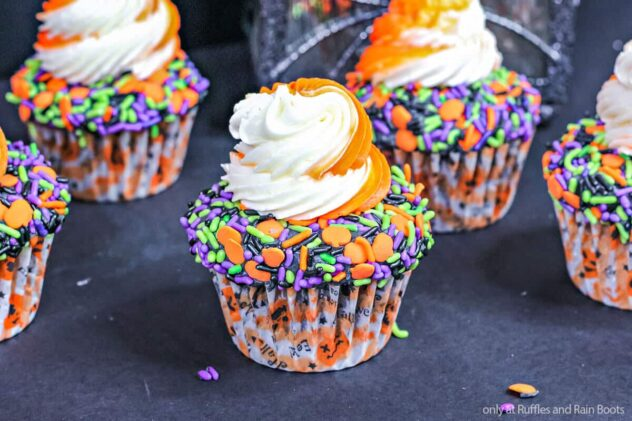 Cupcakes are covered with orange, green, purple, and black sprinkles on top.  In the center is a swirl of orange and white frosting on these Halloween themed cupcakes.