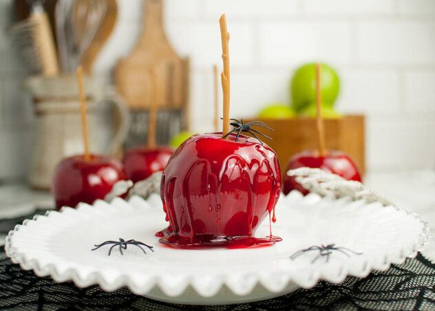 A apple coated in a red candy coating with a stick sitting on a white plate that's decorated with black spiders is the first vegan treat for Halloween.