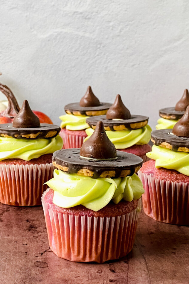 Reddish colored cupcakes frosted with bright green frosting, topped with an iced cookie and a chocolate kiss to create a witches hat on top of this Halloween themed cupcake.