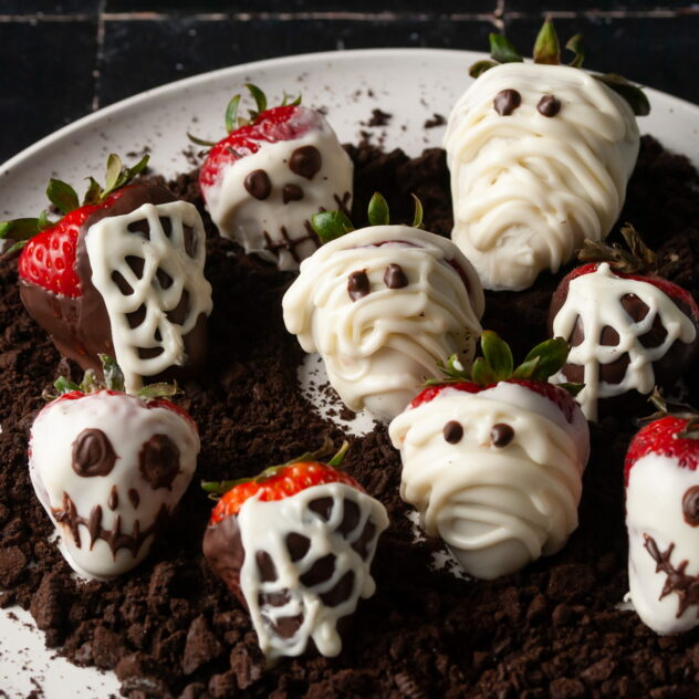 A plate of chocolate covered cherries that have been decorated with a combination of dark and light chocolate to create skull heads, mummies, and spider webs.  This is an adorable fruit based Halloween treat.