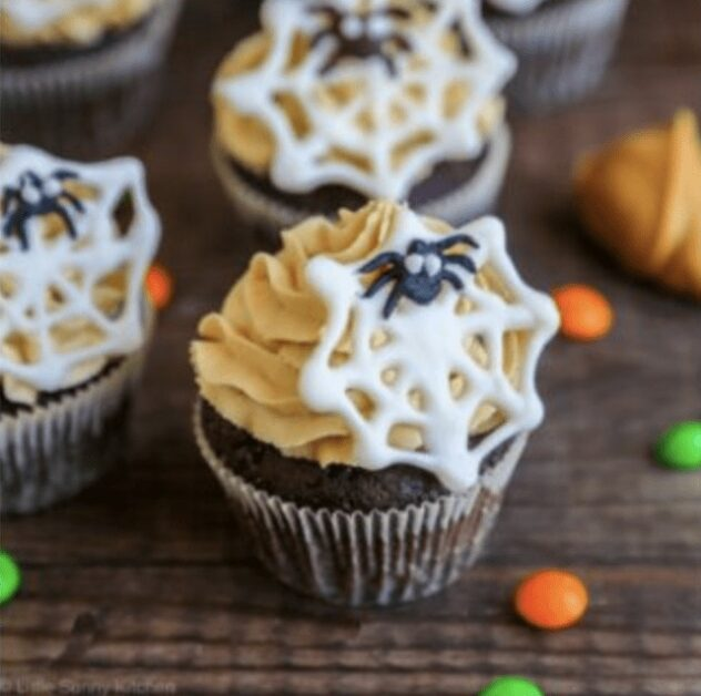 These Halloween themed cupcakes are chocolate cupcakes topped with a light brown peanut butter frosting.  Each cupcake is topped with a white chocolate spider web with a small chocolate spider on it.