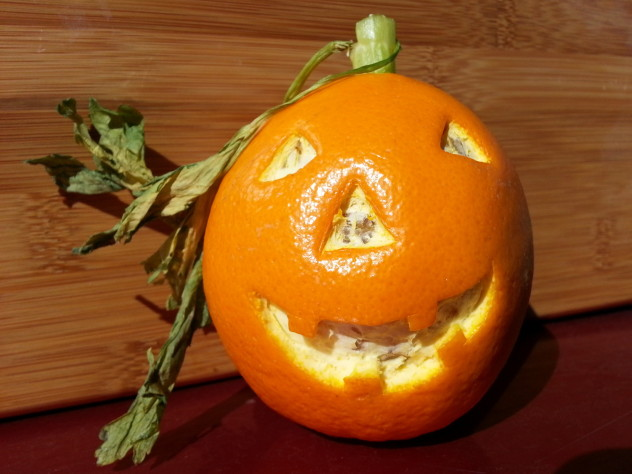 An orange that has had the eyes, nose, and mouth of a jack-o-lantern carved out of the skin of the orange creates a simple vegan Halloween treat.