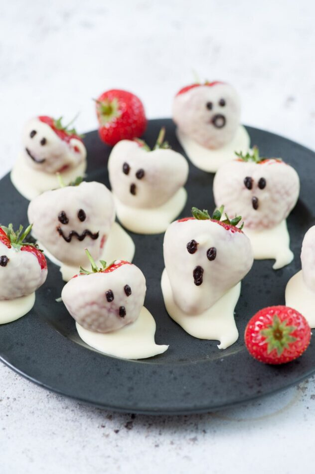 Fruit based Halloween treats such as these fresh strawberries dipped in white chocolate and decorated with chocolate eyes and mouths to make Halloween ghosts.